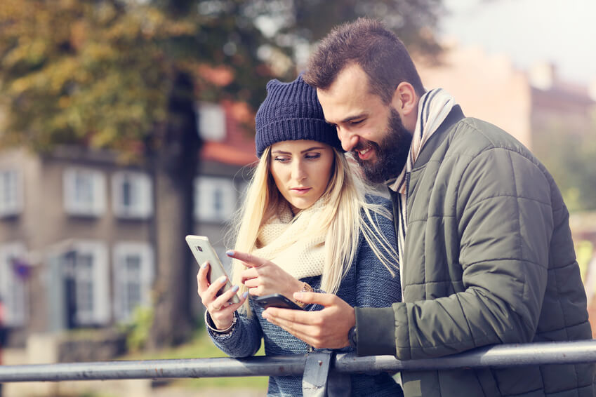 couple interacting over a cell phone on a bridge.