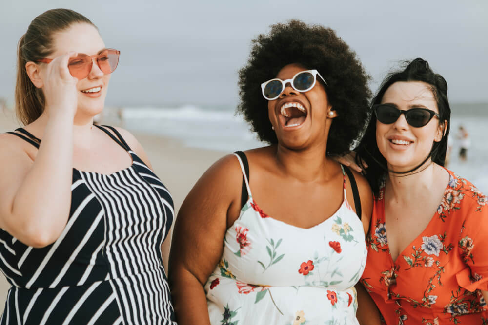 3 beautiful curvy women from different ethnicities backgrounds laughing on the beach