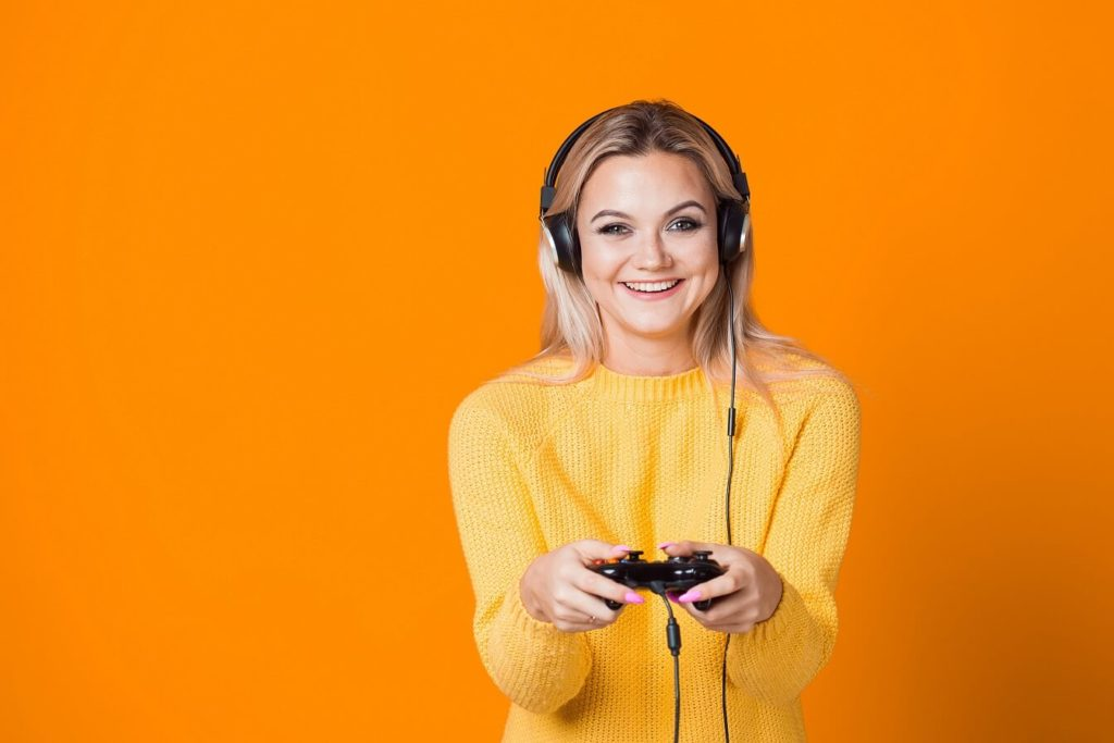 attractive blond gamer girl laughing and posing infront of orange background