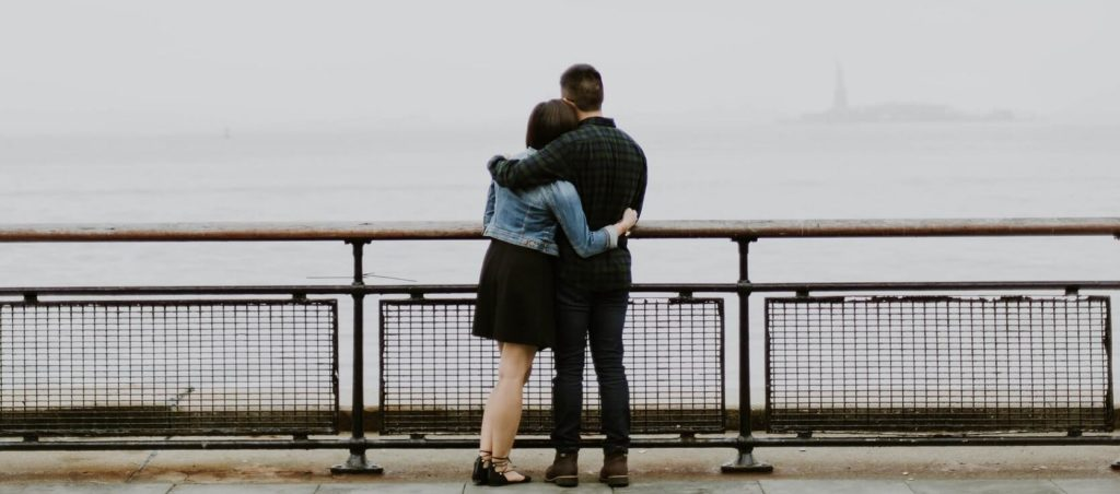 cute couple standing on a bridge