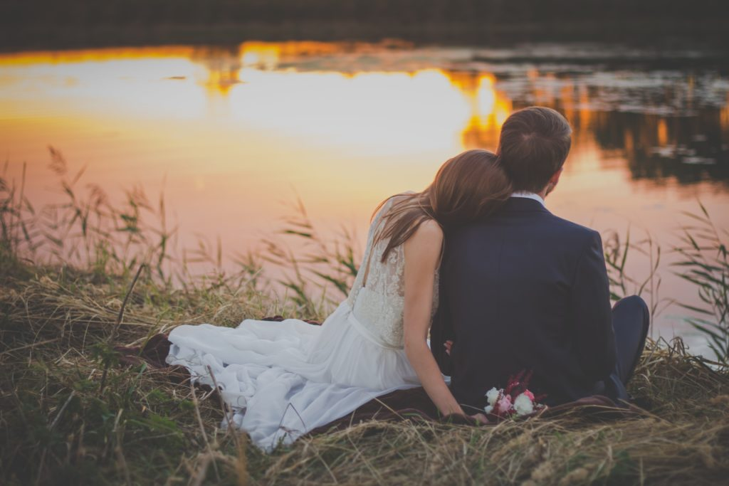 christian couple sitting romantically by a lake