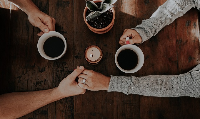 couple holding hands while drinking coffee together
