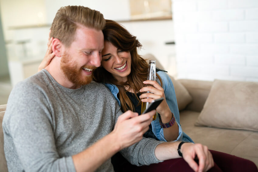 Good looking couple chilling in  the living room and using smart phone together