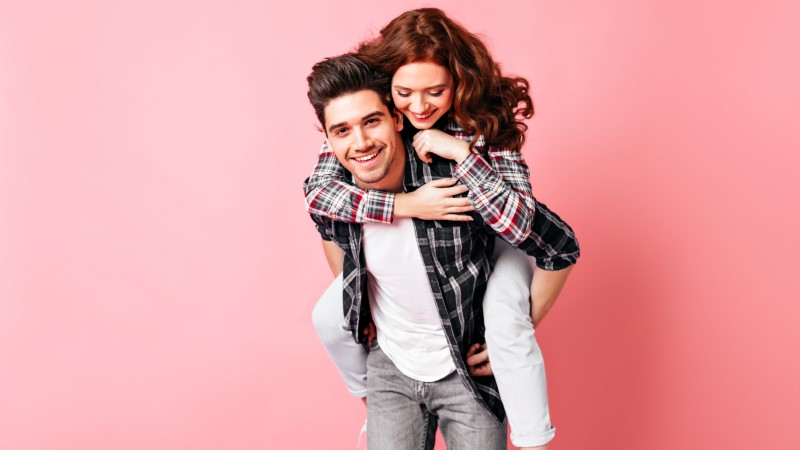 asexual guy happy to give his pretty ginger girlfriend a piggyback ride in front of a pink background