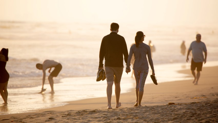 Relaxed couple over 40 is walking on the beach