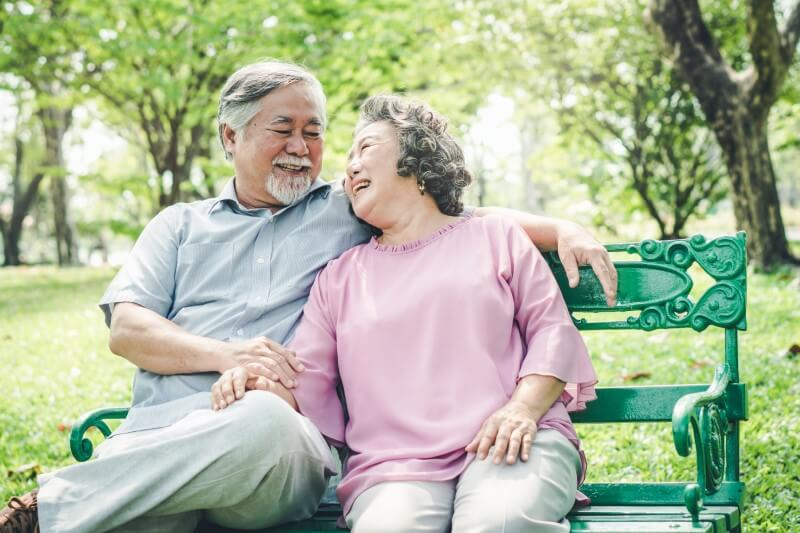 asian seniors have date in the park, sit on a bench laughing
