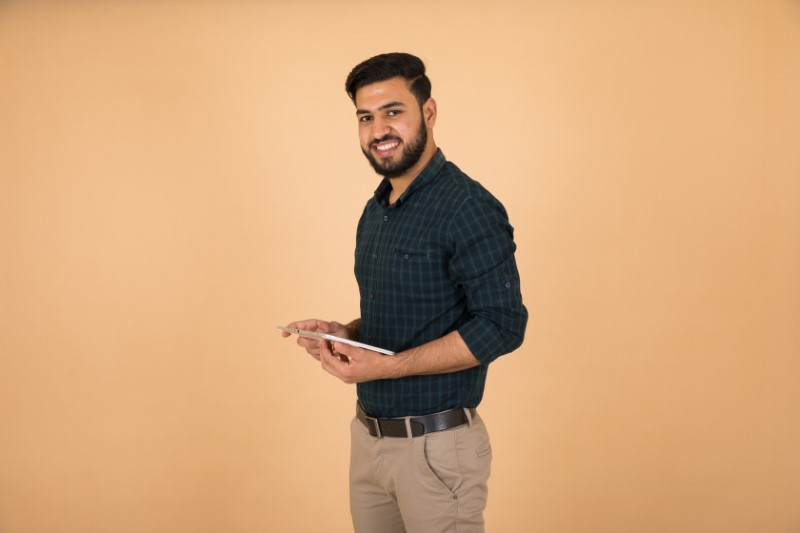 single muslim man holds his tablet