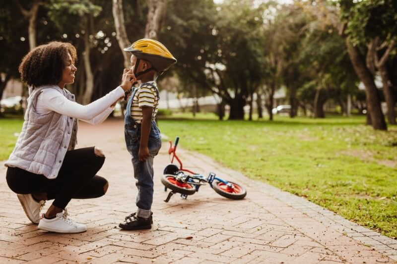 mom helps her son with his bicycle helmet