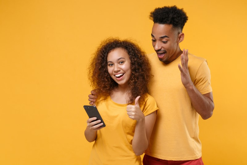 man and woman happy because of dating app on their phone