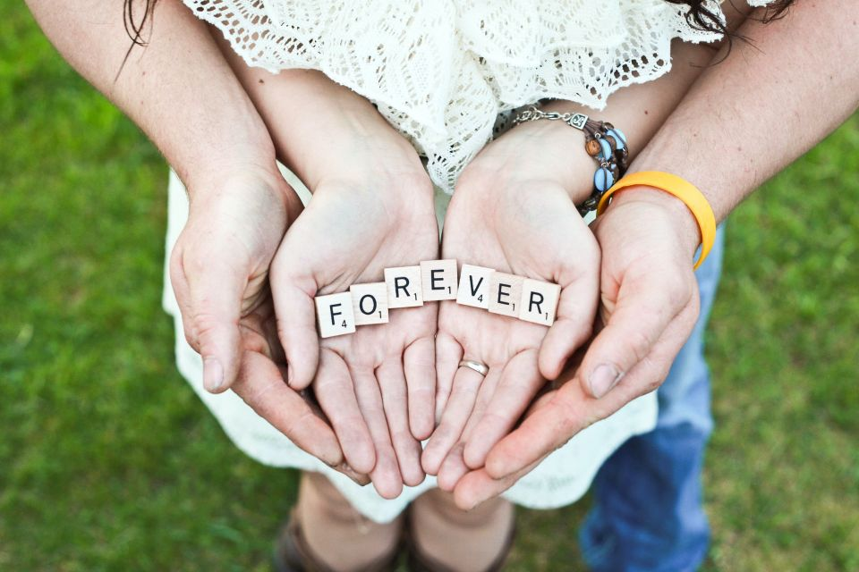 "Couple holding the words ""forever"" in their hands together."
