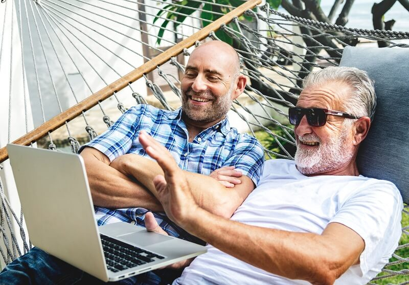 Two older gay men happily using a laptop together.