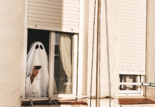 Ghost drinking wine in a window