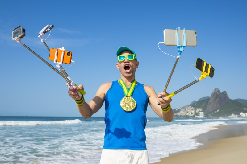 crazy guy takes funny selfie with several selfie sticks on a beach