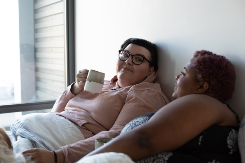 lesbian girlfriends in bed with a cup of coffee