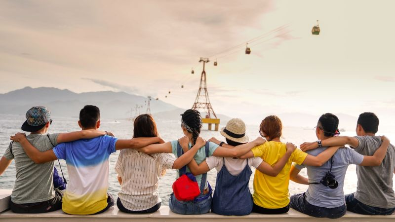 friends sitting together hugging and watching the scenery
