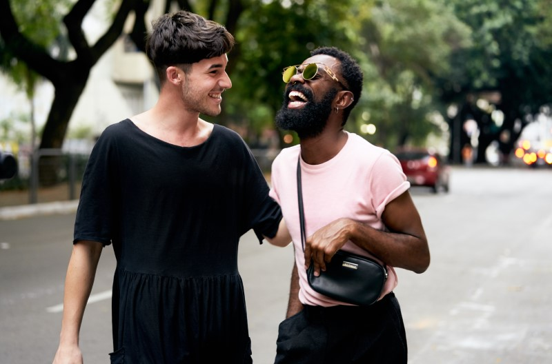 two men laughing together on the street